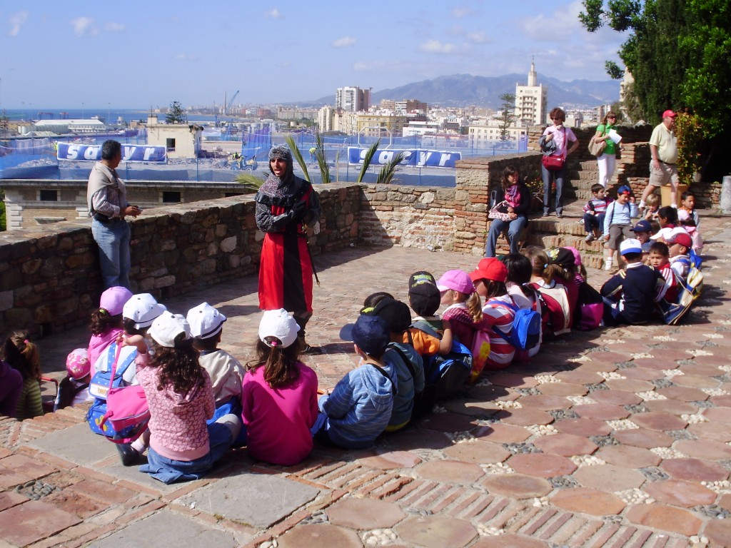 A teacher engages his class in a history lesson at the Alcazaba.