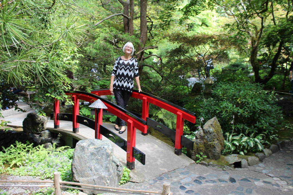 Janis on one of a couple of bright red and black bridges in the japanese Garden