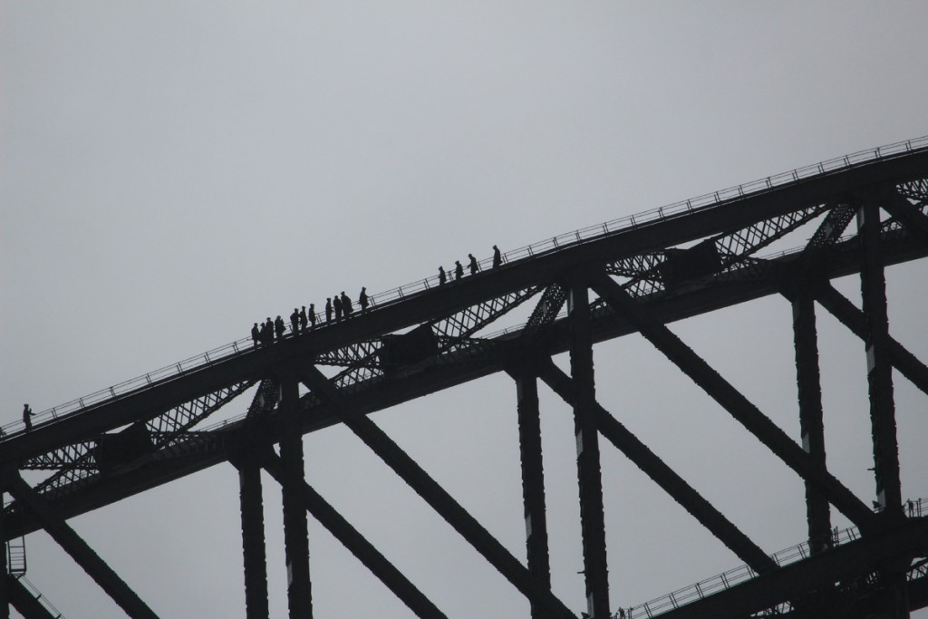 People walking along the arch at the top of the bridge.