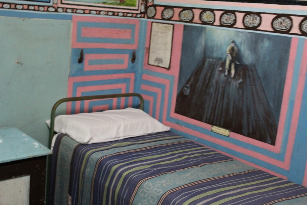 The prisoner's bed with a painting above it.